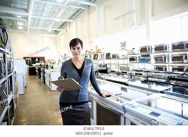 Portrait confident saleswoman with clipboard in appliance store