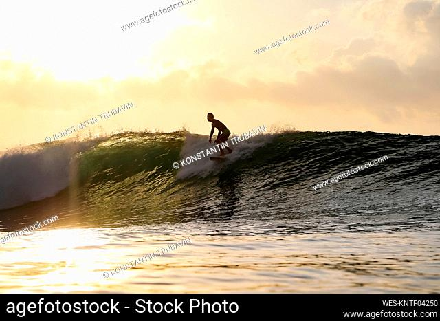 Surfer at sunset, Bali, Indonesia