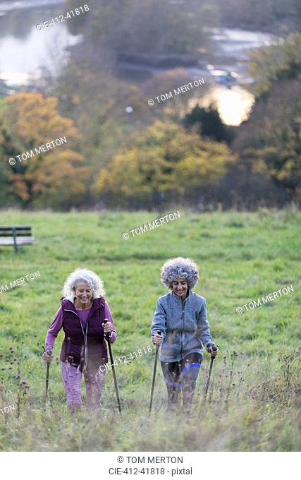 Active senior women friends hiking with poles up rural hillside