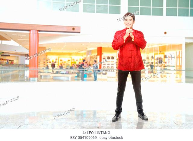 An Asian Chinese man in a cheongsam dress with congratulations gesture. Happy Chinese New Year