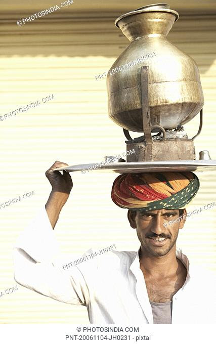 Portrait of a vendor carrying a tea pot on a traditional stove over his head