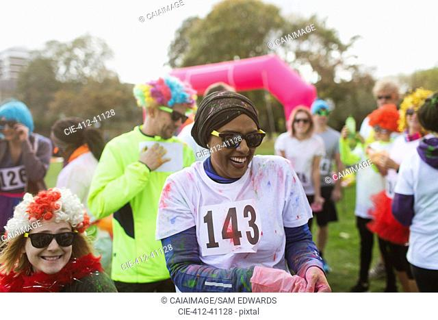 Laughing female runner covered in holi powder at charity run in park