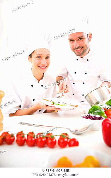 View of Young attractives professionals chefs cooking together