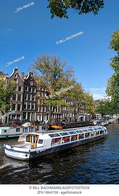 The wonderful canals and buildings beside the river and the tourist boats riding on the water in Amsterdam Holland Netherlands in a sunny day