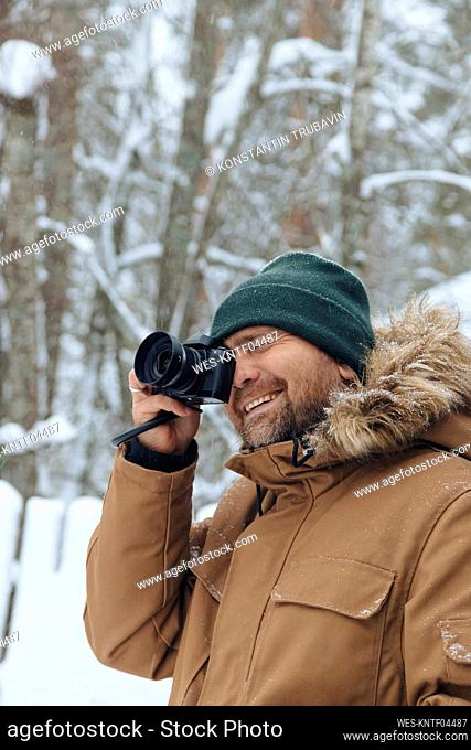 Portrait of relaxed man taking picture with digital camera in winter forest