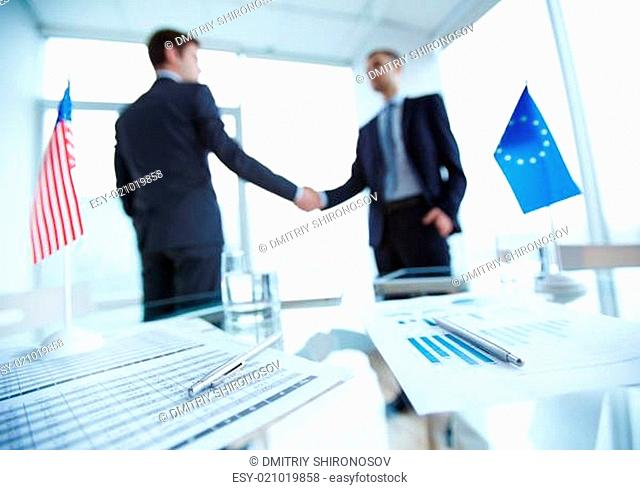 Papers and pens on workplace with two business partners handshaking on background