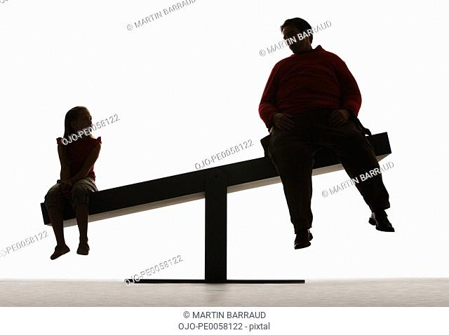 Large man and small girl on unbalanced plank