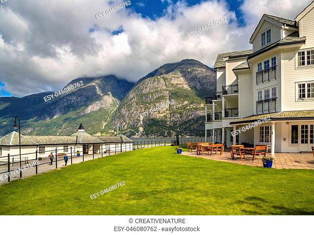 White wooden apartments at fjord in Eidfjord village Hordaland province Norway with mountain background