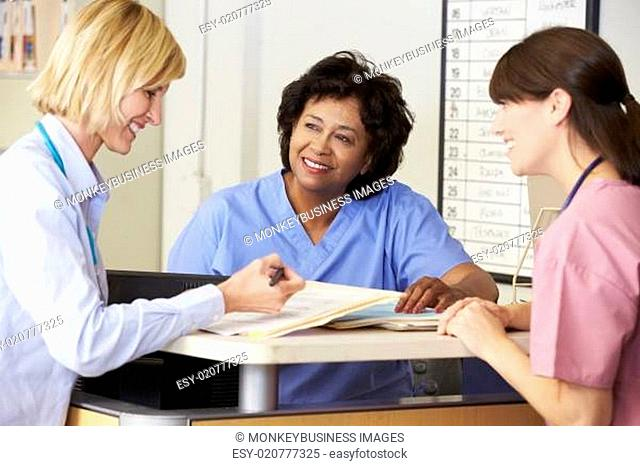 Doctor And Nurses In Discussion At Nurses Station
