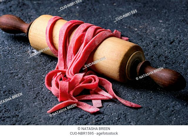 Fresh raw uncooked homemade pink beetroot pasta tagliatelle on wooden rolling pin over dark texture concrete background