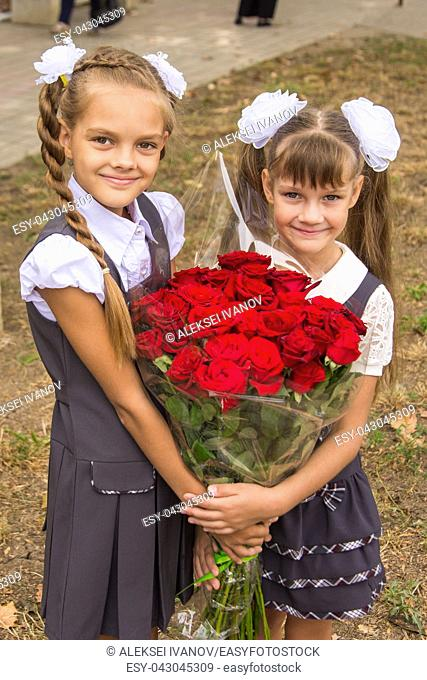 Two schoolgirls are holding a large bouquet of flowers in their hands
