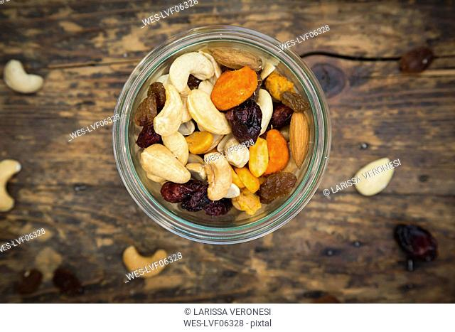 Glass of trail mix on dark wood