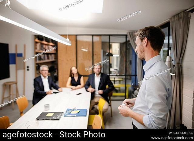 Young entrepreneur holding a presentation in front of business people