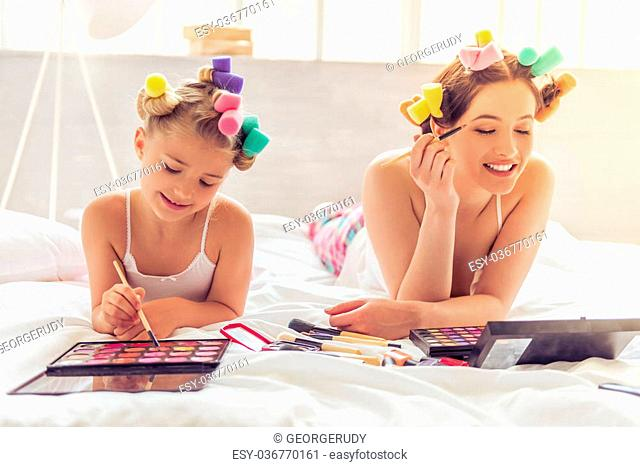 Beautiful young mother and her daughter in pajamas and with hair curlers are doing makeup and smiling, lying on bed at home