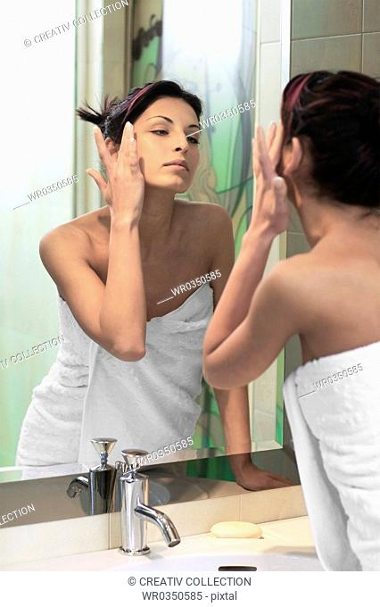 woman taking care of her skin in front of the bathroom mirror