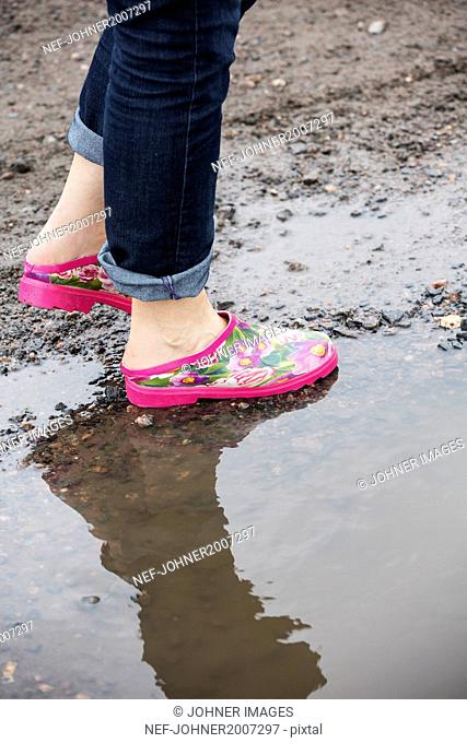 Person in cogs standing in puddle, low section