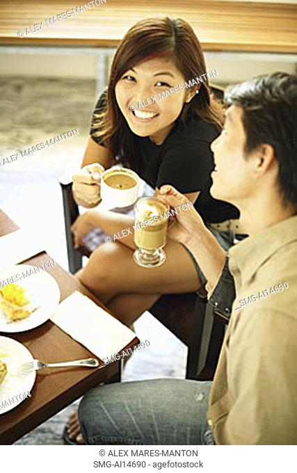 Couple at cafe, holding cups of coffee, woman looking up at camera