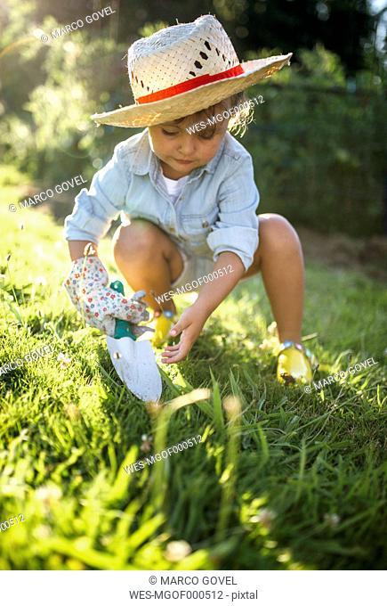 Little girl crouching with gardening glove and hand trowel on a meadow