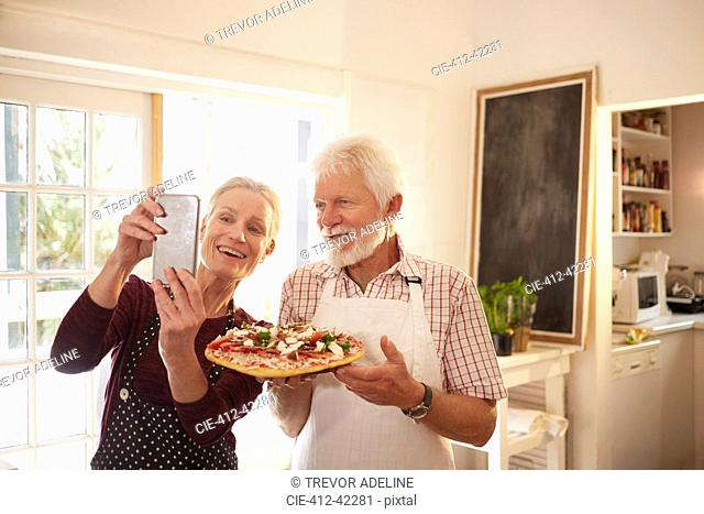 Smiling, confident senior couple taking selfie with pizza at cooking class