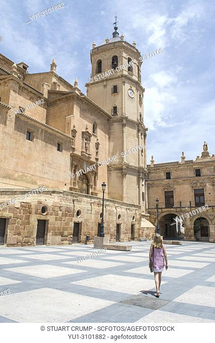 Female tourist walking in the by the colegiata de San Patricio church in the plaza de espana in Lorca Murcia Spain