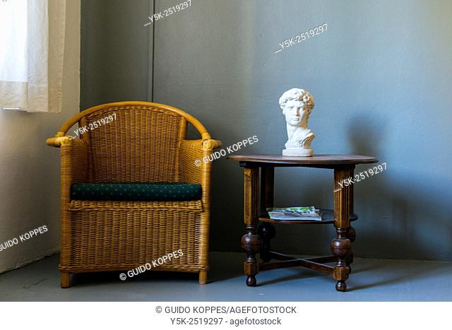 Tilburg, Netherlands. Rattan chair and antique wooden table, forming a small seating inside a photographers studio