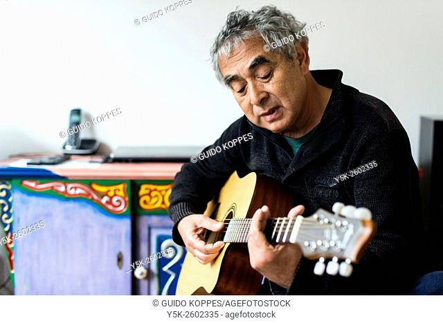Tilburg, Netherlands. Middle aged man playing acoustic guitar in his living room