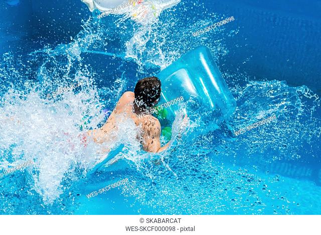 Man in the pool on airbed, moving, water splashes