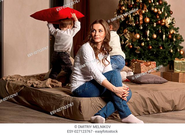 Happy family are playing on a bed near Christmas tree at home. Merry Christmas and Happy New Year. Beautiful young mother with two sons