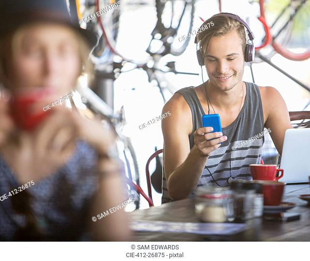 Young man with headphones and laptop texting with cell phone in cafe