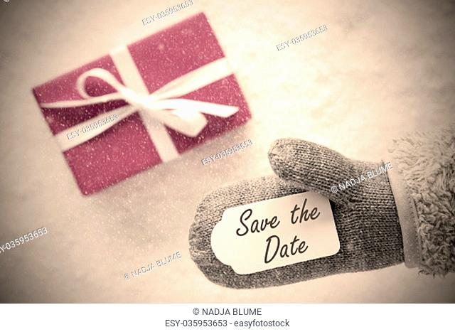 Glove With Label With English Text Save The Date. Pink Or Rose Gift Or Present On Snow In Background. Seasonal Greeting Card With Snowflakes And Instagram...