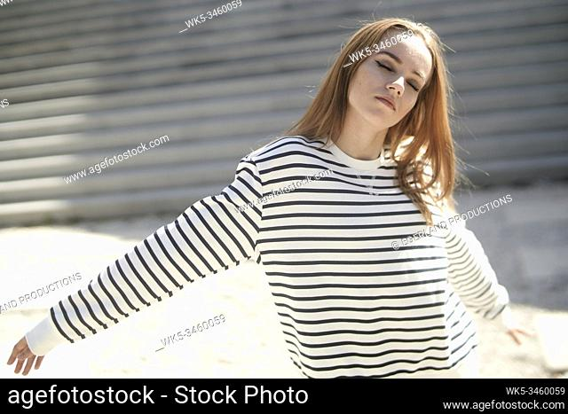 Young woman dancing on the street, absent-minded