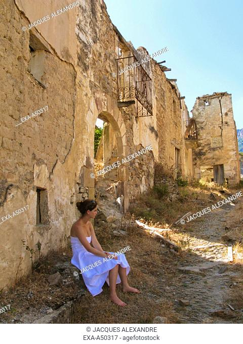 Young woman sitting in front of some ruins