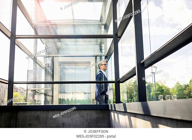 Mature businessman at glass structure in the city looking around