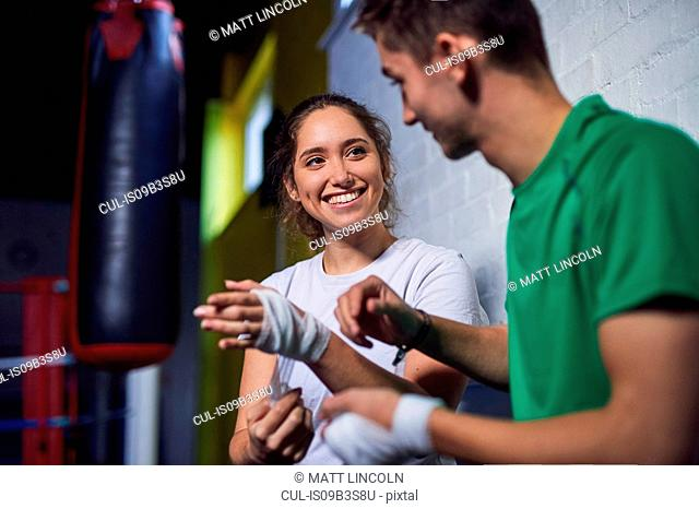 Young male and female boxers chatting while bandaging hands