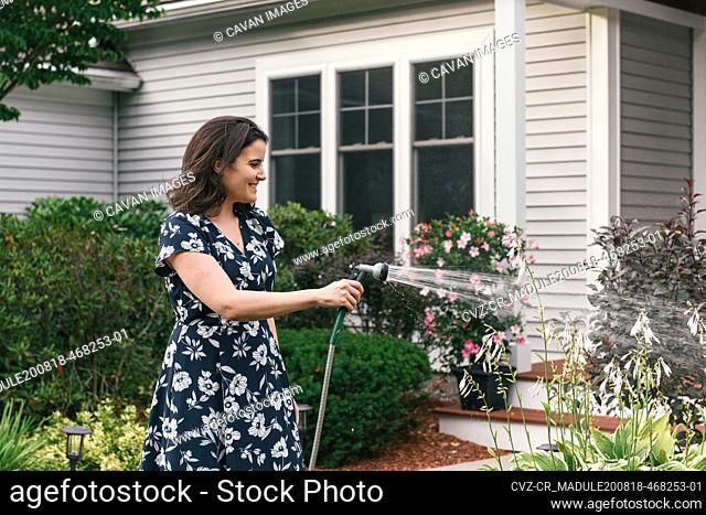 Adult woman smiling while watering plants with hose in front of home