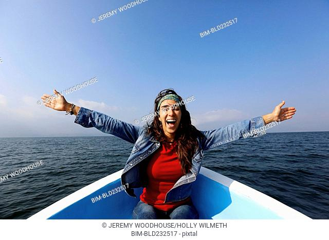 Carefree woman sitting in boat with arms outstretched
