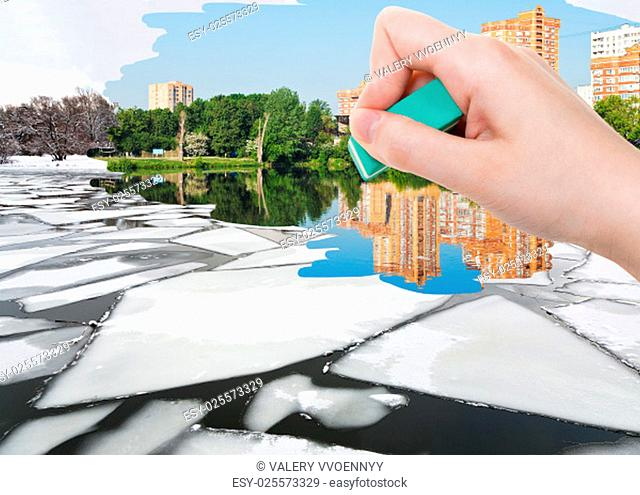 weather concept - hand deletes ice floe near river waterfront in winter by rubber eraser from image and summer cityscape are appearing