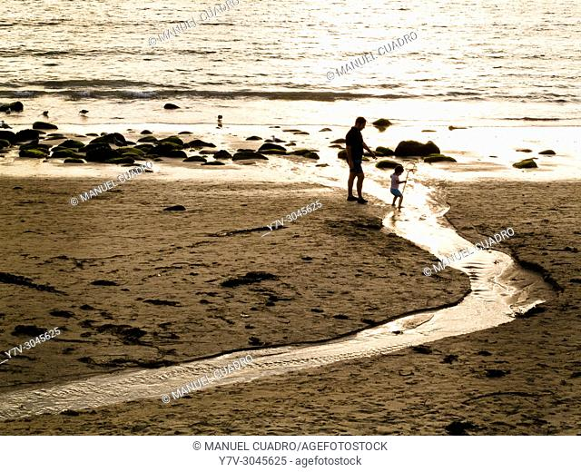 Father and son at sunset, Portosín Beach, Galicia, Spain