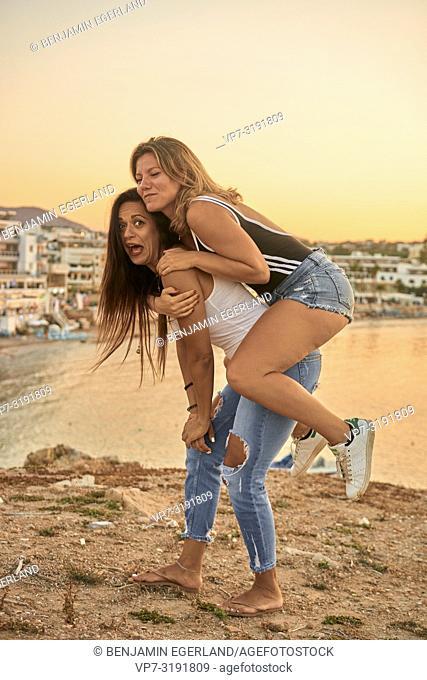 two women, piggypack, friends, joking, adventure, in Chersonissos, Crete, Greece