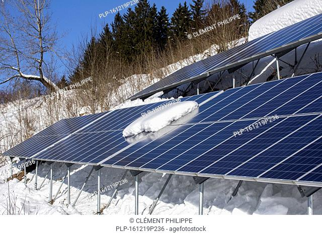 Solar panels in the snow in winter of photovoltaic power station / solar park for the supply of electricity