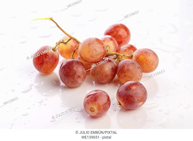 bunch of grapes in white base with water droplets wet