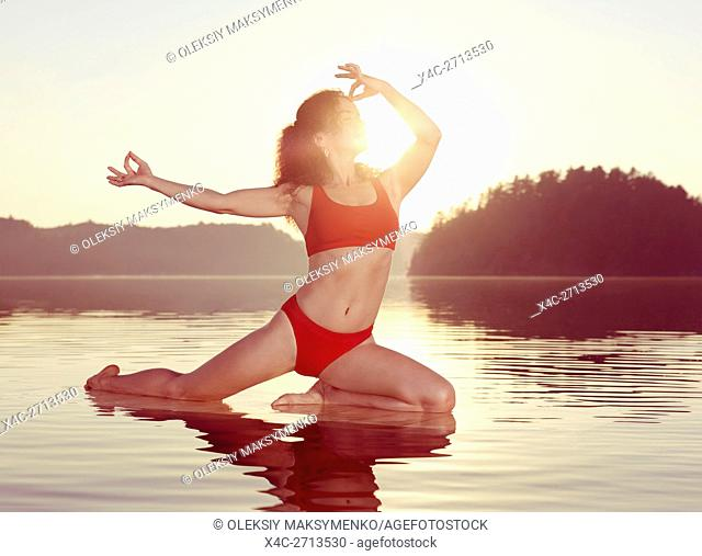 Young woman practicing Hatha yoga on a floating platform in water on the lake in early morning sun light. Yoga Pigeon posture variation, Kapotasana