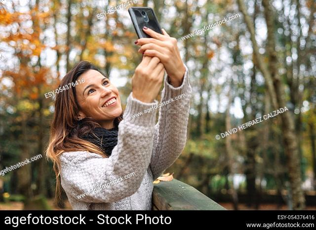 Portrait of Happy woman making selfie in the autumn park full of yellow leaves