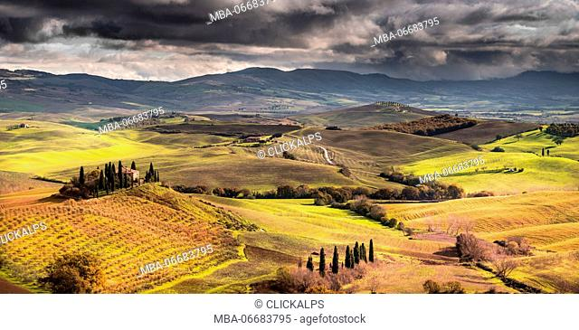 San Quirico d'Orcia, Tuscany, Italy. Sunlight over the farmhouse and the hill