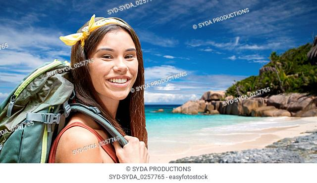 happy woman with backpack over seychelles beach