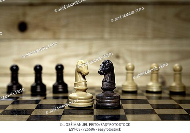 Faced chess horses and chess pawns with chess board