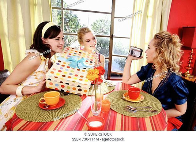 Two young women holding a gift with another young woman videotaping them