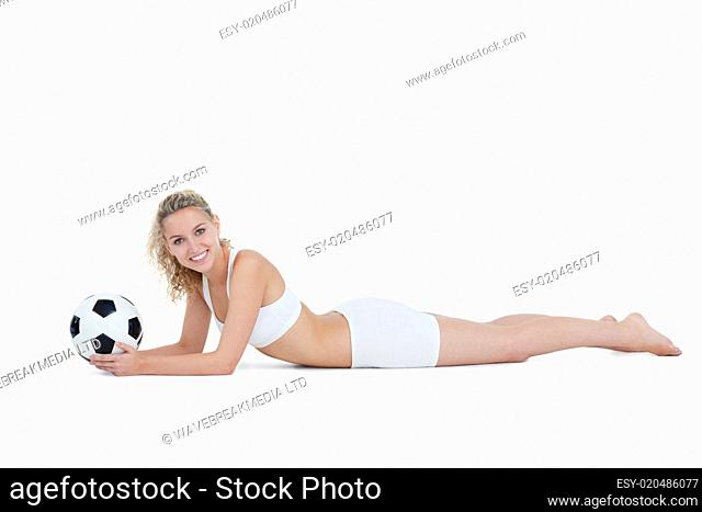 Young smiling woman lying down while holding a football