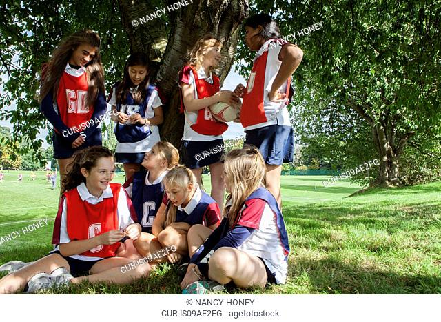 Teenage schoolgirl netball team taking a break