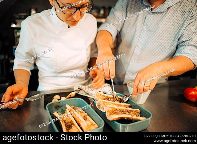 Couple of chefs working together while preparing food in restaurant